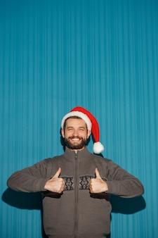 Sonriente hombre de navidad con un gorro de papá noel en el fondo azul.