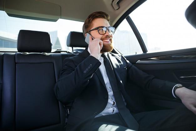 Sonriente hombre de negocios barbudo en anteojos hablando por teléfono celular