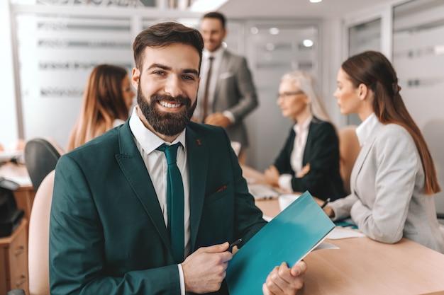 Sonriente hombre de negocios caucásico barbudo en ropa formal con pluma y carpeta
