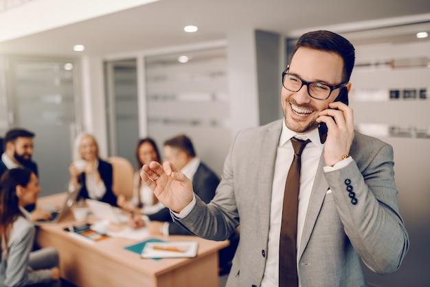 Sonriente hombre de negocios caucásico guapo en ropa formal de pie en la sala de juntas y hablando por teléfono.