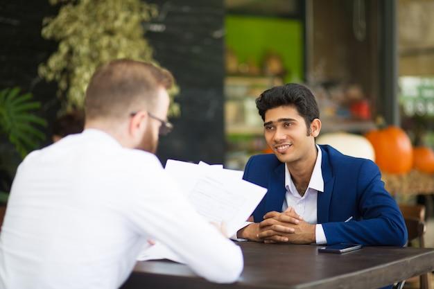 Sonriente hombre de negocios esperando cuando socio de lectura contrato