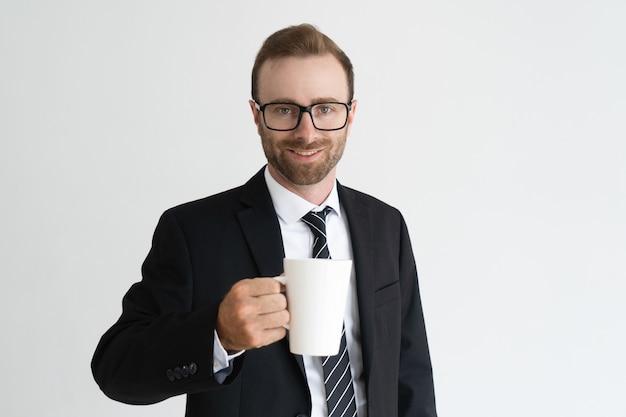 Sonriente hombre de negocios guapo sosteniendo la taza, beber té y mirando a cámara.