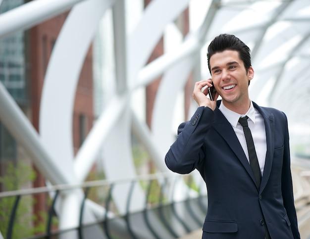 Sonriente hombre de negocios hablando por teléfono móvil en la ciudad