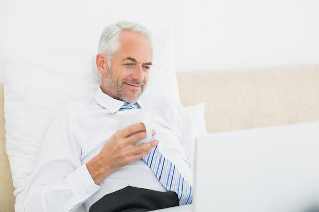 Sonriente hombre de negocios maduro usando la computadora portátil en la cama