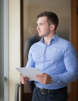 Sonriente hombre de negocios de pie junto a la ventana en la oficina y leyendo el papel