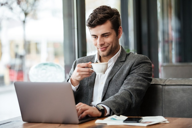Sonriente hombre de negocios sentado junto a la mesa en la cafetería y usando la computadora portátil