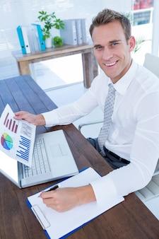 Sonriente hombre de negocios trabajando con diagramas de flujo