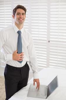 Sonriente hombre de negocios usando la computadora portátil en la habitación del hotel
