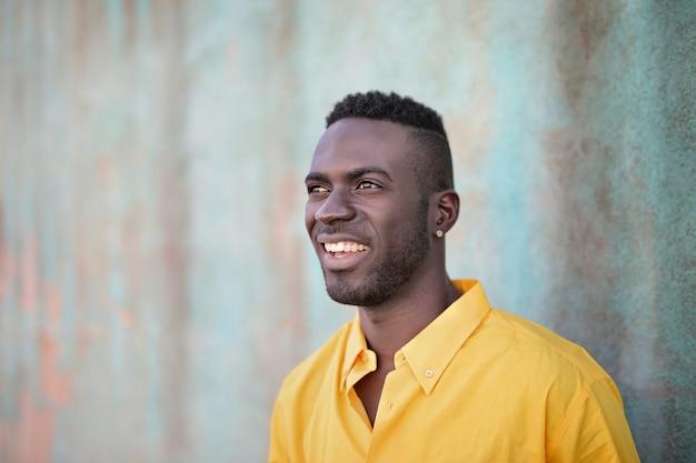 Sonriente hombre negro de pie detrás de una pared.