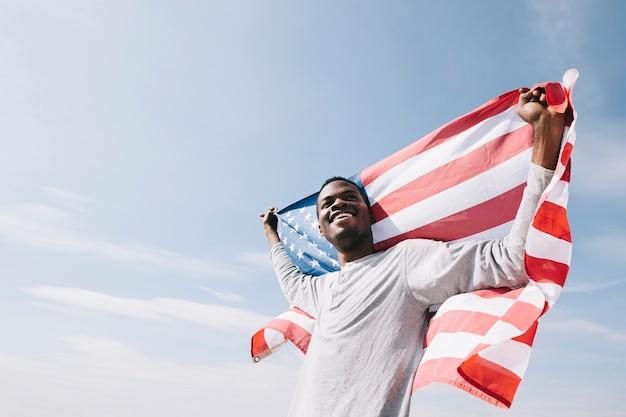 Sonriente hombre negro sosteniendo ondeando una bandera estadounidense detrás de la espalda