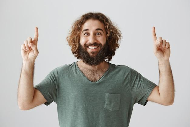 Sonriente hombre de oriente medio barbudo apuntando con el dedo hacia arriba