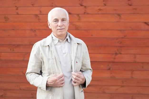 Sonriente hombre de pelo gris atractivo de pie junto a la pared mirando a la cámara con copyspace