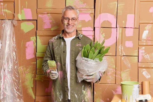 Sonriente hombre de pelo gris en ropa casual renueva las paredes de pinturas de casa en un apartamento nuevo