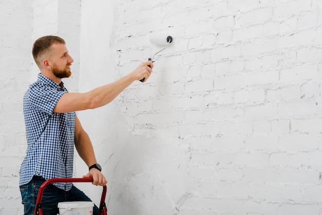 Sonriente hombre pintando la pared
