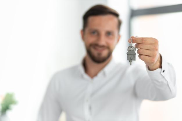 Sonriente hombre de raza caucásica inquilino o inquilino mostrar las llaves de la casa. el agente o corredor de bienes raíces masculino tiene las llaves del espectáculo para la nueva casa o apartamento. comprar un nuevo concepto de hogar