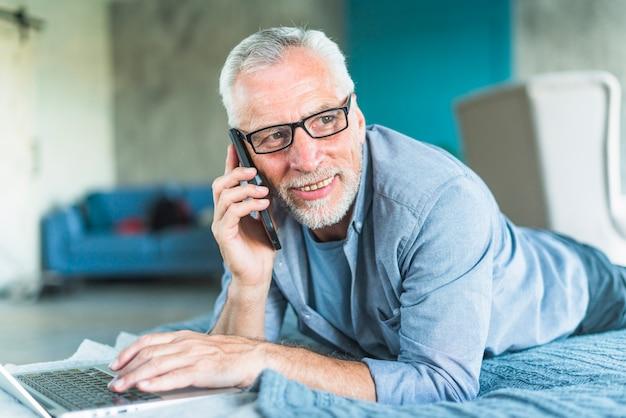 Sonriente hombre senior acostado sobre la cama con la computadora portátil hablando por teléfono móvil