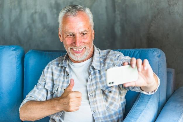Sonriente hombre senior sentado en el sofá mostrando el pulgar arriba signo mientras toma selfie