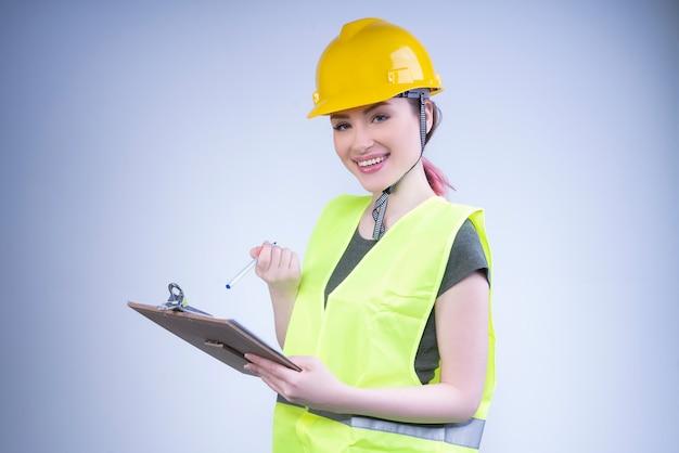 Sonriente ingeniera en un casco amarillo toma notas