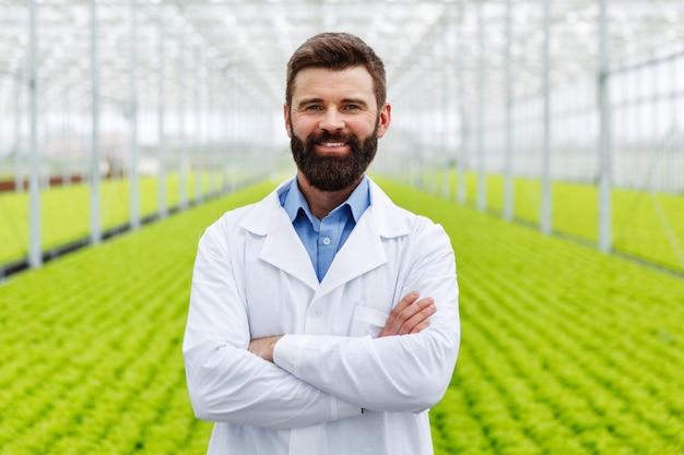 Sonriente investigador masculino con barba se encuentra ante las plantas en un invernadero