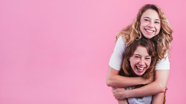 Sonriente joven abrazando a su amiga por detrás contra el fondo rosa