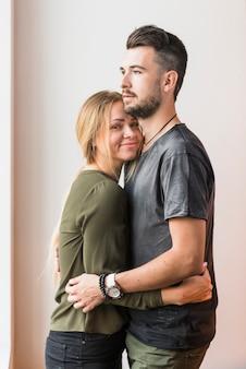 Sonriente joven abrazando a su novio contra el fondo beige