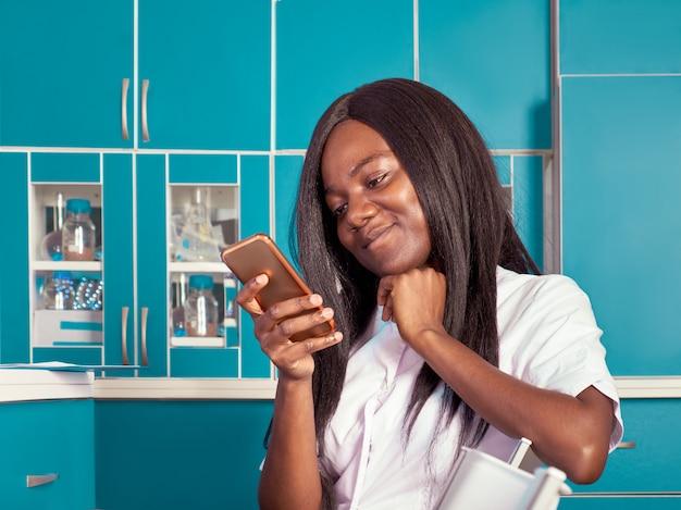 Sonriente joven africana, científico, estudiante de medicina, investigador utiliza teléfono móvil