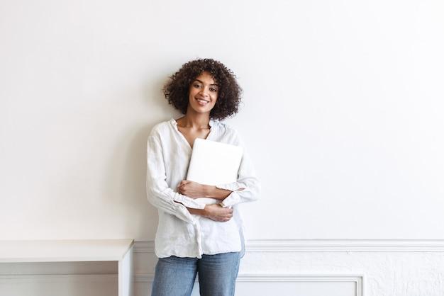 Sonriente joven africana de pie en la pared blanca en el interior, sosteniendo la computadora portátil