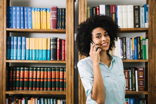 Sonriente joven afroamericana hablando por teléfono inteligente cerca de libros