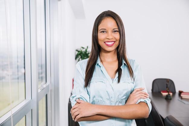 Sonriente joven afroamericana junto a la ventana