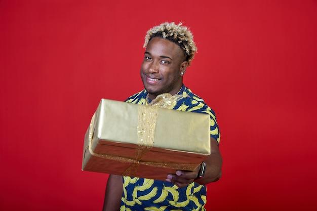 Sonriente joven afroamericano da un regalo en un paquete de oro sobre un fondo rojo.