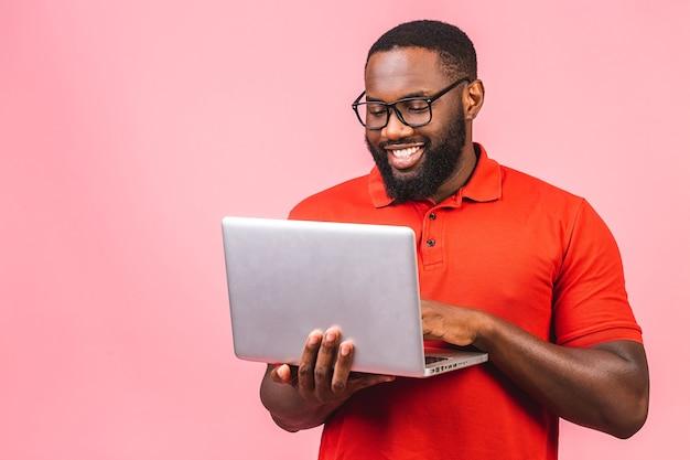 Sonriente joven afroamericano de pie y usando la computadora portátil