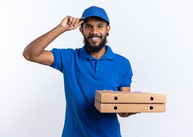 Sonriente joven afroamericano repartidor sosteniendo cajas de pizza y poniendo la mano en su gorra aislado sobre fondo blanco con espacio de copia