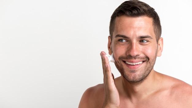 Sonriente joven aplicando espuma de afeitar sobre fondo blanco