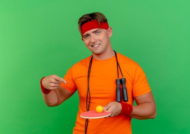 Sonriente joven apuesto deportivo con diadema y muñequeras con saltar la cuerda alrededor del cuello sosteniendo y apuntando a la raqueta de ping pong con pelota aislada en la pared verde