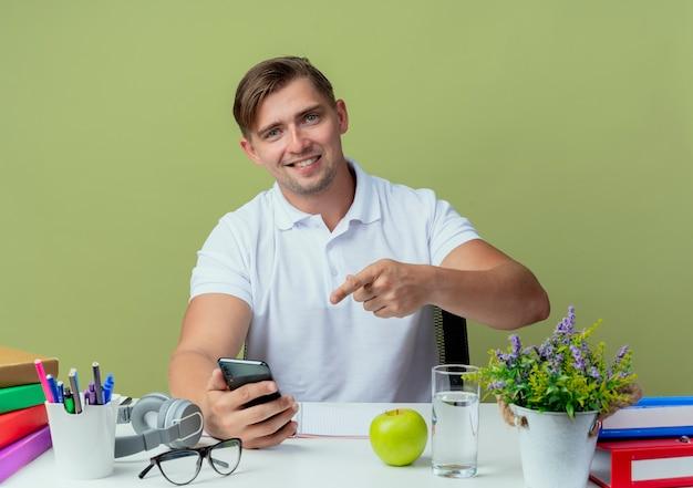 Sonriente joven apuesto estudiante sentado en el escritorio con herramientas escolares sosteniendo y puntos en el teléfono aislado en verde oliva