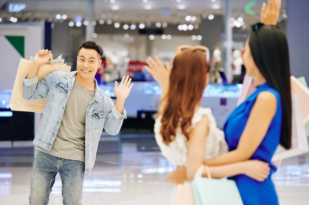 Sonriente joven apuesto hombre asiático saludando con la mano a sus amigas en el centro comercial