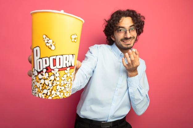 Sonriente joven apuesto hombre caucásico con gafas mirando a la cámara estirando el cubo de palomitas de maíz hacia la cámara con una pieza de palomitas de maíz en otra mano aislada sobre fondo carmesí con espacio de copia