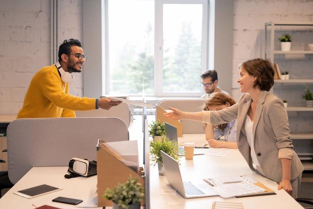 Sonriente joven apuesto hombre de oriente medio de pie en la mesa en la oficina de espacios abiertos y pasando documentos comerciales sobre la partición de la mesa a un colega