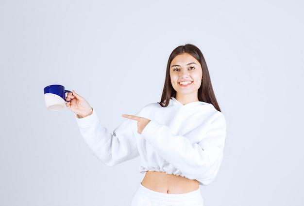 Sonriente joven apuntando a una taza sobre fondo blanco-gris.