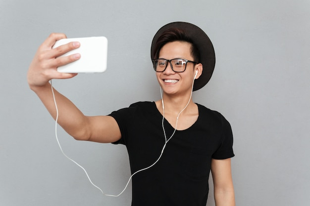 Sonriente joven asiática escuchando música y hacer selfie