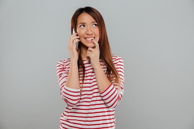 Sonriente joven asiática hablando por teléfono