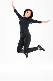 Sonriente joven asiática saltando
