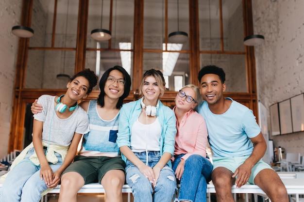 Sonriente joven asiático con gafas abrazando suavemente a una chica de piel marrón clara. retrato interior de estudiantes contentos divirtiéndose en la biblioteca mientras se preparan para los exámenes.
