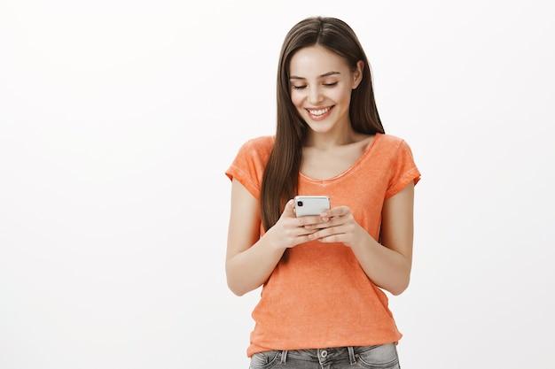 Sonriente joven atractiva mediante teléfono móvil