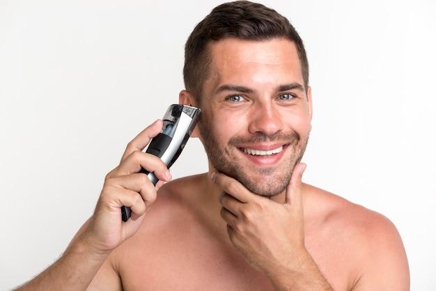 Sonriente joven barba de afeitar con máquina de afeitar eléctrica sobre fondo blanco.