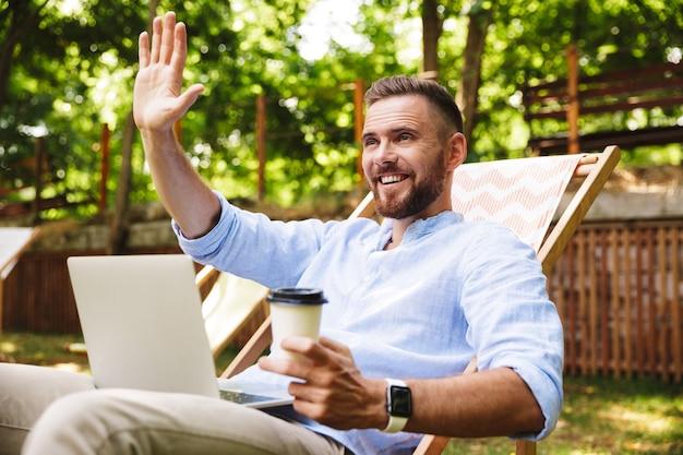 Sonriente joven barbudo emocional agitando sosteniendo café.