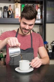 Sonriente joven barista masculino preparar café