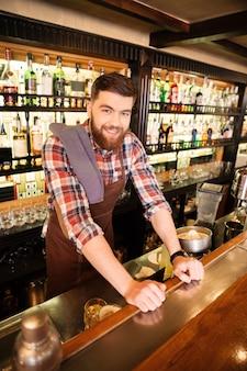 Sonriente joven barman barbudo de pie en el pub