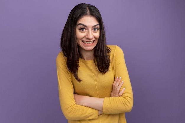 Sonriente joven bastante caucásica de pie con postura cerrada aislado en la pared púrpura con espacio de copia