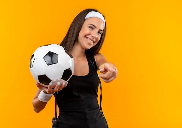 Sonriente joven bastante deportiva con diadema y muñequera sosteniendo un balón de fútbol y apuntando con saltar la cuerda alrededor de su cuello aislado en el espacio naranja